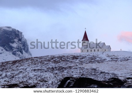 Vintage church on snowy hill top during dawn hours