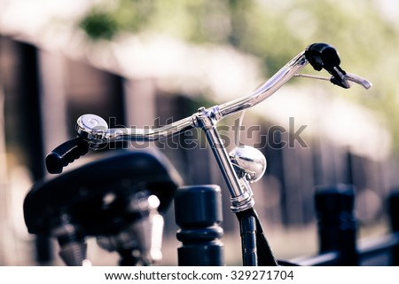 Vintage city bike colorful retro light and handlebar on street, alternative ecology transportation, commute on classic bicycle in urban scene, blurred bokeh background. Selective focus on handlebar.