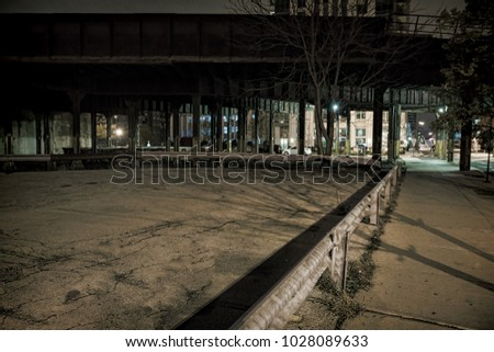 Vintage city railroad bridge next to an empty urban lot at night.