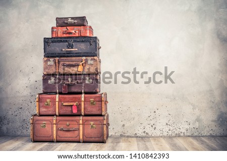 Vintage classic outdated trunks luggage with tags, old antique leather suitcases tower front concrete wall background. Travel baggage concept. Retro style filtered photo  Stock photo ©