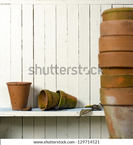 Vintage clay flowerpots on shelf; displayed in casual arrangements against rustic wall; good copy space