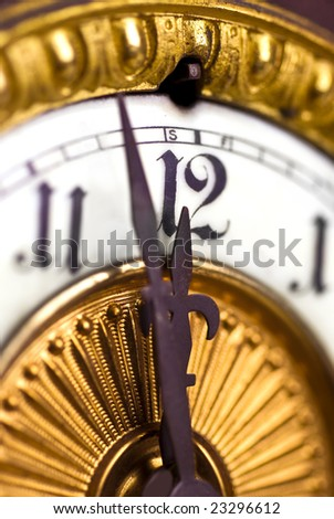 vintage clock face showing a few minutes to midnight; differential focus; 'New Year's Eve'