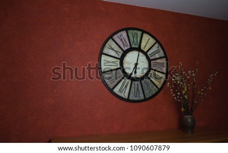 Vintage clock on a red wallpaper with catkins in the foreground  Stock foto ©