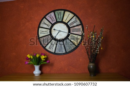 Vintage clock on a red wallpaper with tulips and catkins in the foreground  Stock foto ©