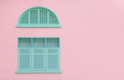 Vintage closed green mint shutters and wooden windows isolated on pink background with copy space and clipping path.