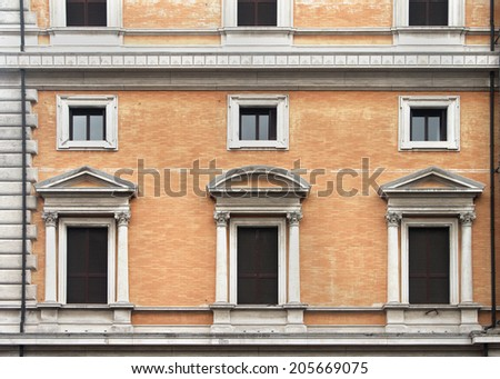 Vintage closed windows on old building stone facade