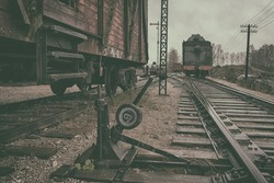 Vintage coach stands on the vintage railway station with iron rails on the background of the locomotive and poles with wires