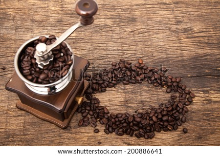 Vintage coffee bean grinder next to circle shape coffee beans on wooden table top as background