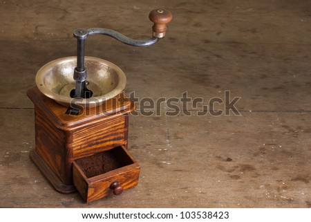 Vintage coffee grinder on old wooden table. Antique, XIX century