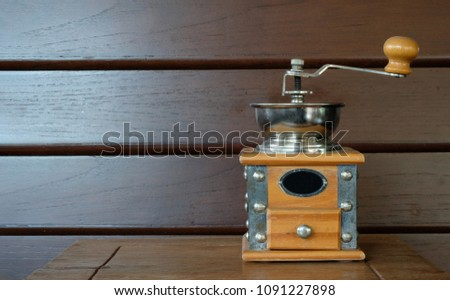 vintage coffee grinder with a metal bowl on a wooden table and wall background #1091227898