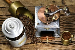 vintage coffee grinder with manufacture roasted Indonesian Arabica coffee beans on rustic wooden background