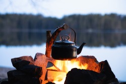 Vintage coffee pot on camping fire. Wonderful evening atmospheric background of campfire. Romantic warm place with fire. The concept of adventure, travel, tourism and camping.