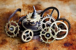Vintage cogs gears wheels collection set. Aged clockwork mechanism parts macro view. Different cogwheels teeth shapes objects with textured metal surface. Shallow depth of field photo