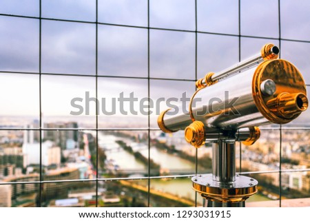 Vintage coin operated binocular overlooking for Paris from top of Eiffel Tower. Monocular telescope at observation deck for tourist viewer looking out to city in spring cloudy day. Vision. France.