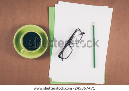 Vintage color. Mobile with blank paper or notebook and cup of coffee. Simple workspace or coffee break with relaxing composing. Blank paper and colorful pencils on the wooden table. View from above