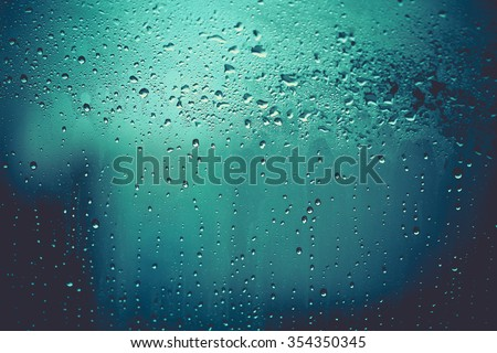 vintage color tone of Water and rain drops on the glass, abstract view, Drops of rain on blue glass background / drops on glass after rain. Image has shallow depth of field.  #354350345