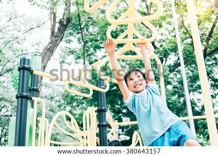 Vintage color tone, Young asian boy hang the yellow bar by his hand to exercise at out door playground under the big tree.