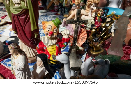 Vintage colorful clown figure raising his fist amongst other religious porcelain and bronze statuettes standing on the ground at an antiques flea market in Lisbon.