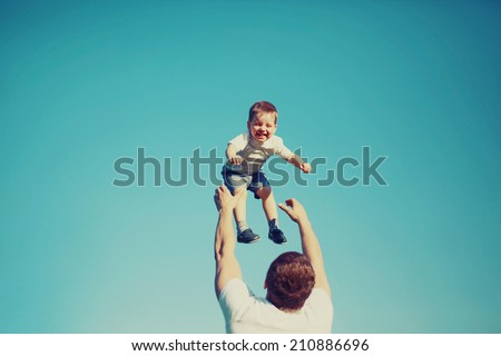 Vintage colors photo happy father and child having fun outdoors, carefree, blue sky, family, travel, vacation, childhood, father\'s day - concept