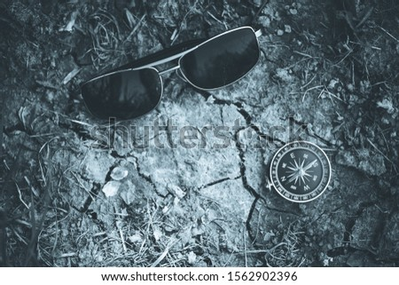 Vintage compass and sunglasses lying on the floor. Adventure and discovery concept.