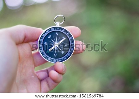 Vintage compass in man's hand, adventure and discovery concept
