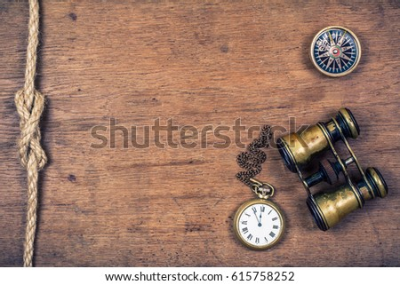 Vintage compass, old pocket watches, aged binoculars, rope knot on rustic oak wooden textured table background. Retro style filtered photo