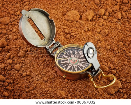 vintage compass on red marsian soil - stock photo