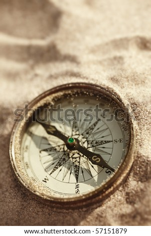 vintage compass on the sand with natural sun light, selective focus
