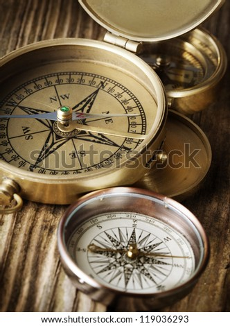 Vintage compasses on wood background
