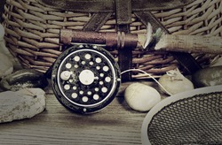 Vintage concept, to include grain effect, of a wet antique fly fishing reel, rod, landing net, artificial flies and rocks in front of creel with rustic wood underneath. Layout in horizontal format.