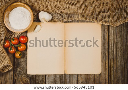 Vintage cookbook with cooking ingredients background. Top view photograph with kitchen utensils on vintage, natural, raw, wooden background with visible texture.
