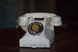 Vintage corded phone light beige with dialer on a dark background.