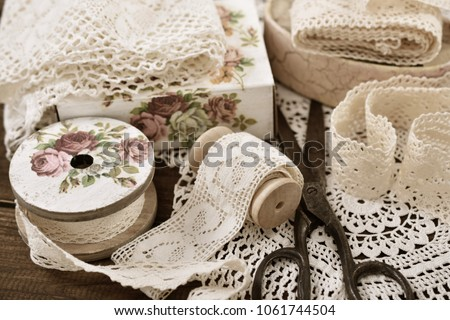vintage cotton lace trims on wooden spools and sewing items lying on the table