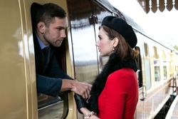 Vintage couple, man in uniform, woman in red dress, holding hands goodbye at train station as train is about to leave