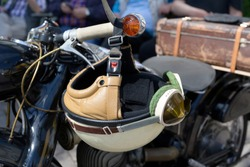 vintage crash helmet is hanging on the handlebar of a classic oldtimer motorbike, selected focus