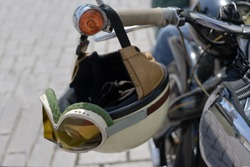 vintage crash helmet is hanging on the handlebar of a classic oldtimer motorbike, selected focus, narrow depth of field