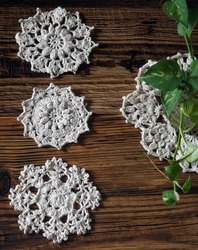 Vintage crochet doilies on rustic wooden surface. Classic yet old fashioned style. Small size, flat lay.