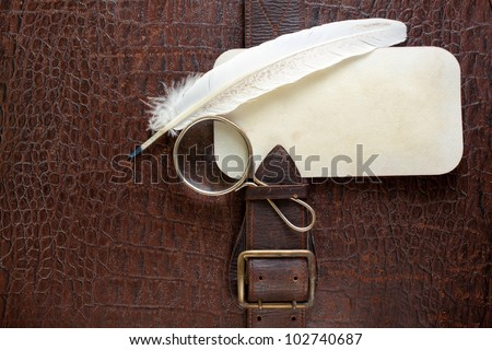 Vintage crocodile leather textured background with magnifying glass, quill and paper frame - stock photo