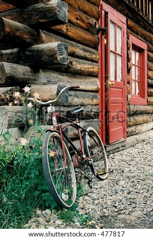 Vintage Cruiser Bicycle leaning against a log cabin