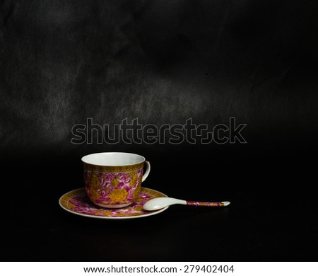 vintage cup, saucer and spoon on a black background