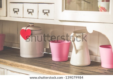 vintage cupboard with jars and heart shaped decorative sign