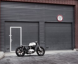 Vintage custom motorcycle motorbike caferacer in front of rolled gates. Ready for a wild ride.