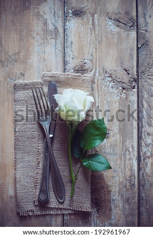 Vintage cutlery, antique silverware, fork, knife and a rose flower with rough cloth on an old wooden background