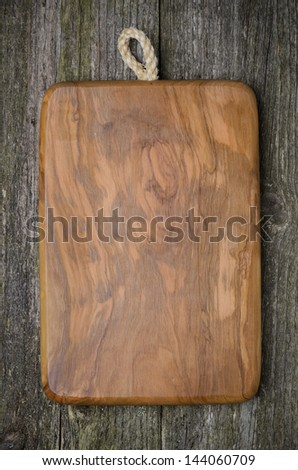 vintage cutting board with space for text on old wooden background, close-up