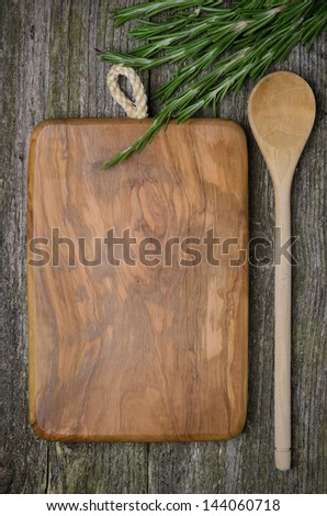 vintage cutting board with space for text, spoon and fresh rosemary on old wooden background, vertical