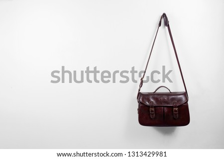 Vintage dark brown leather shoulder bag hanging on a white wall, for camera, general miscellaneous items. #1313429981