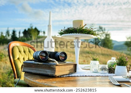Vintage decor for photo session in the mountains: table with book, candlesticks and binoculars