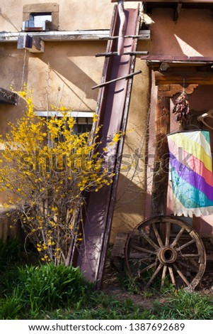 Vintage decoration in New Mexico. Old wooden wheel and adobe house