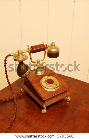 Vintage dial telephone, made from rich timber and brass, resting on antique telephone table.