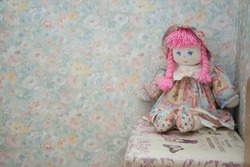 Vintage doll on a flowers wall-paper